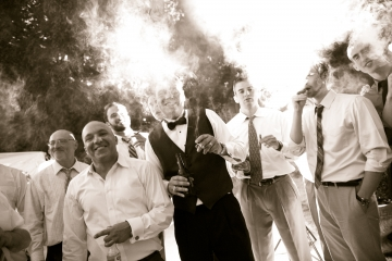 Groomsmen smoking cigars at wedding